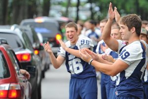 Members of the football team greet arriving students