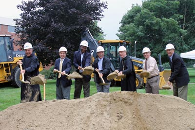 College officials and other representatives participate in a ceremonial groundbreaking